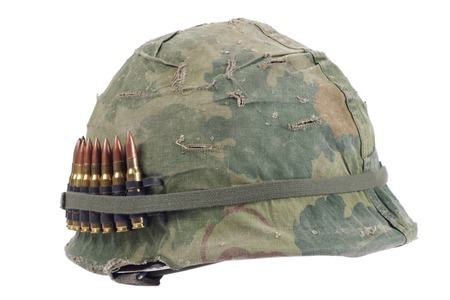 US Army helmet with camouflage cover and ammo belt - Vietnam war period isolated