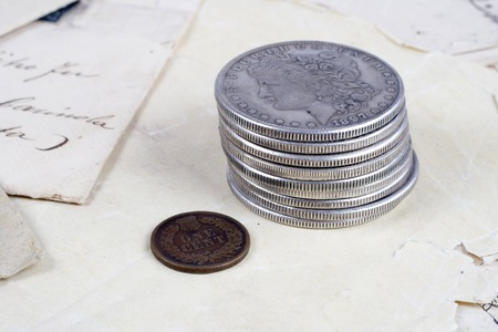 silver coins: stack of silver dollar coins with copper cent on old paper