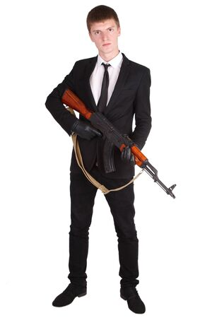 akm: man in black suit and ak 47 isolated on white
