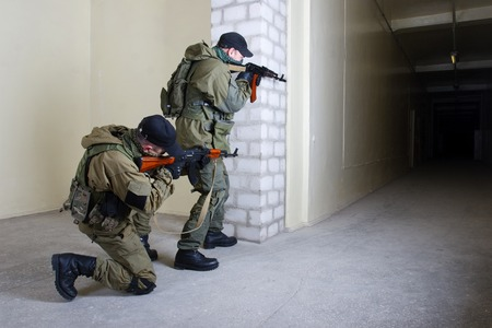 mercenary: mercenary with AK rifle inside the building Stock Photo
