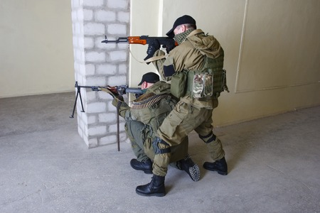 ak 47: insurgents with AK 47 ang RPD gun inside the building