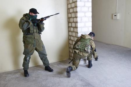 mercenary: mercenary with AK rifle throw a grenade inside the building