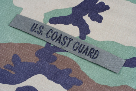 coast guard: KIEV, UKRAINE - June 6, 2015. US COAST GUARD branch tape on woodland camouflage uniform Editorial
