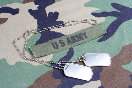 us army: KIEV, UKRAINE - June 6, 2015. US ARMY branch tape and dog tags on woodland camouflage uniform