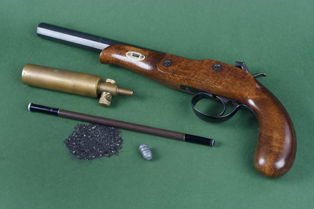 flintlock: Old duel pistol with an accessory on green background Stock Photo