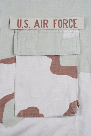 animal private: KIEV, UKRAINE - May 9, 2015. US AIR FORCE branch tape on desert camouflage uniform background