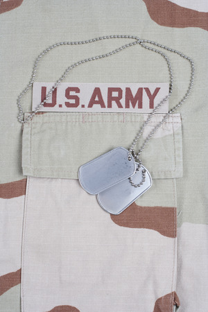 animal private: KIEV, UKRAINE - May 9, 2015. US ARMY branch tape with dog tags on desert camouflage uniform background