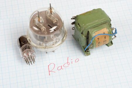 broadcasting: old vacuum tube (electron tube) and transformer on graph paper background