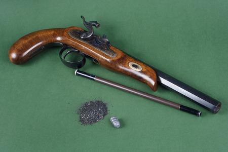 flint gun: Pistola vieja duelo con un accesorio en el fondo verde