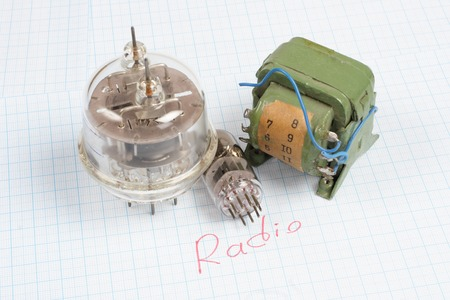 cathode: old vacuum tube (electron tube) and transformer on graph paper background