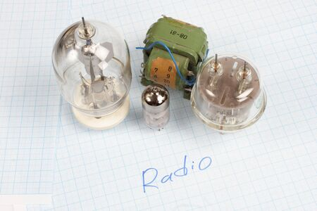 electron: old vacuum tube (electron tube) and transformer on graph paper background