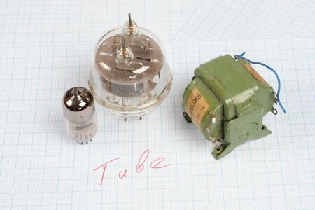 triode: old vacuum tube (electron tube) and transformer on graph paper background