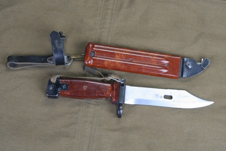 bayonet: early type bayonet with saw rifle on khaki uniform background