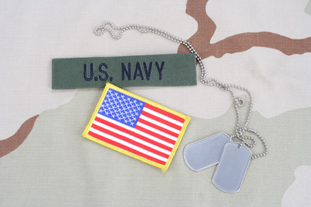 KIEV, UKRAINE - June 14, 2015.  US NAVY branch tape with dog tags and flag patch on desert camouflage uniform