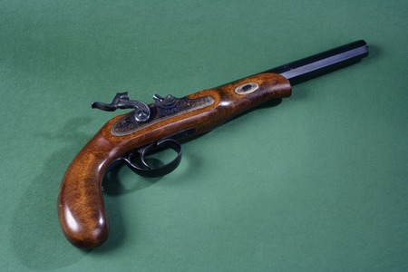 dueling pistol: Old duel pistol on green background