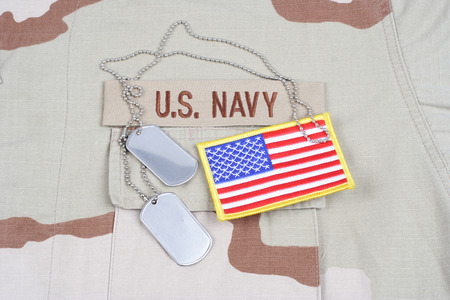 KIEV, UKRAINE - May 9, 2015. US NAVY branch tape with dog tags on desert camouflage uniform background