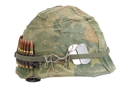 war and military: US Army helmet with camouflage cover and ammo belt and dog tags - Vietnam war period