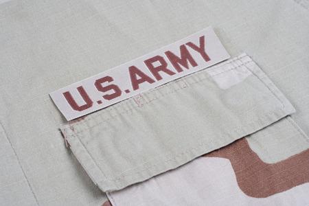 animal private: KIEV, UKRAINE - May 9, 2015. US ARMY branch tape on desert camouflage uniform background