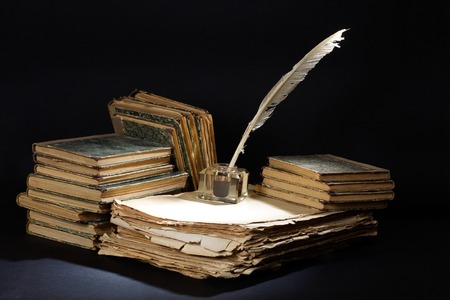 manuscript: Old fountain pen, books and inkwell on a black textured background