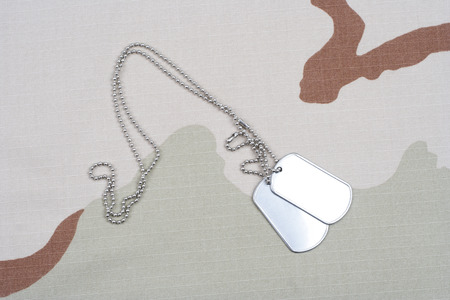 camouflaged: army camouflaged uniform with blank dog tags background
