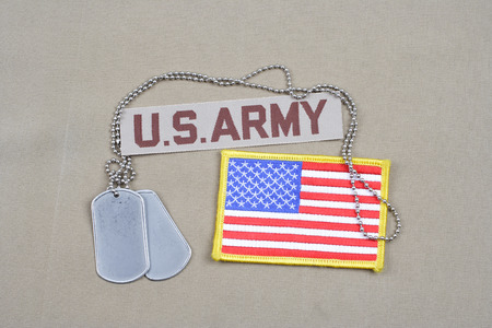 us army: KIEV, UKRAINE - May 9, 2015. US ARMY branch tape with dog tags on uniform background