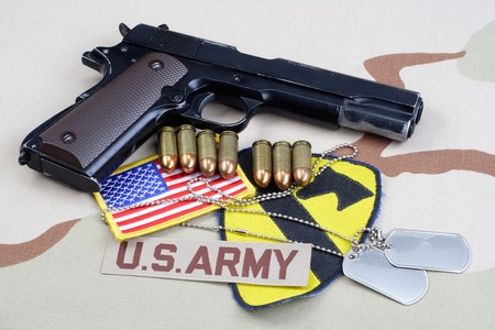 45 gun: KIEV, UKRAINE - May 18, 2015. US ARMY 1st Cavalry Division patch with dog tags, colt government M1911 on desert uniform