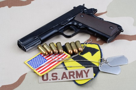 45 pistol: KIEV, UKRAINE - May 18, 2015. US ARMY 1st Cavalry Division patch with dog tags, colt government M1911 on desert uniform