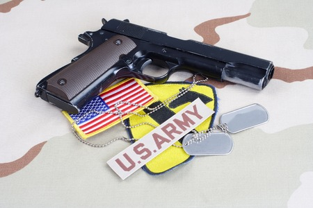KIEV, UKRAINE - May 18, 2015. US ARMY 1st Cavalry Division patch with dog tags, colt government M1911 on desert uniform