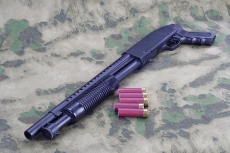 ammunition: pump shotgun with ammunition on camouflaged background