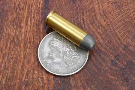 45 ammo: The .45 Revolver cartridges and Silver Dollar Wild West period on wooden background