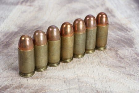 45 gun: The .45 caliber cartridge on wooden background Stock Photo
