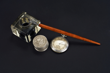 Old fountain pen and inkwell with silver coins and pocket watch on a black textured background