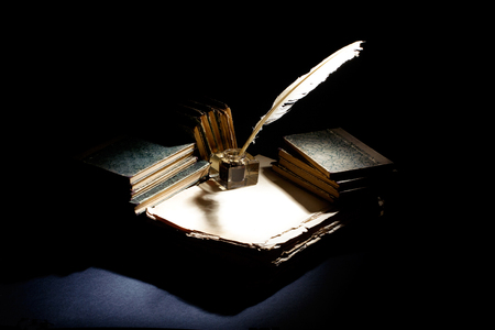 Old fountain pen, books and inkwell on a black textured background