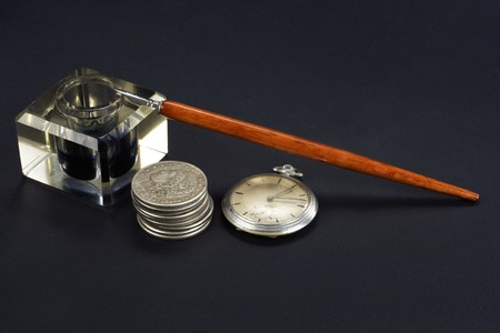 old time: Old fountain pen and inkwell with silver coins and pocket watch on a black textured background