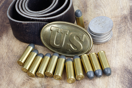 45 ammo: US Belt Buckle Civil War period with revolver cartridges on wooden background