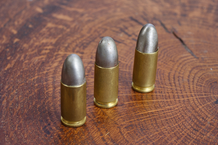 The 9mm caliber cartridge on wooden background