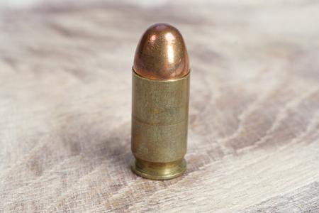 45 ammo: The .45 caliber cartridge on wooden background Stock Photo