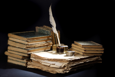 Old fountain pen, books and inkwell and silver coins on a black textured background