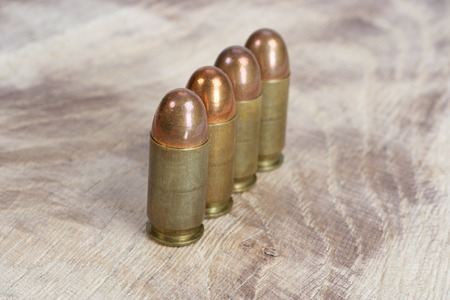 caliber: The .45 caliber cartridge on wooden background Stock Photo
