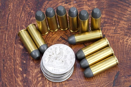 silver state: The .45 Revolver cartridges and Silver Dollar Wild West period on wooden background