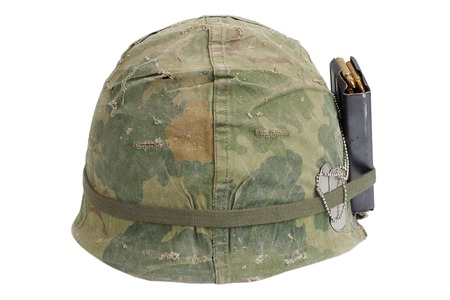 m16 ammo: US Army helmet Vietnam war period with camouflage cover, magazine with ammot and dog tags isolated on white