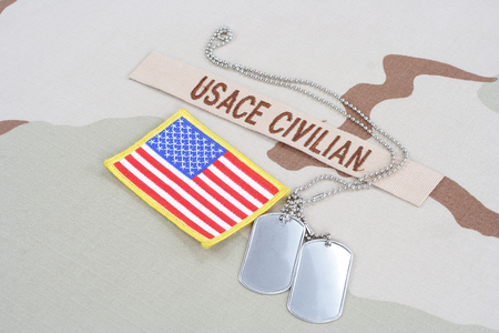 civilian: KIEV, UKRAINE - June 14, 2015. USACE CIVILAN branch tape with dog tags  and flag patch on desert camouflage uniform