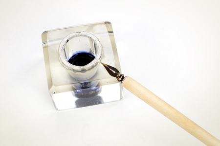 Old fountain pen and inkwell on a white textured background