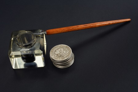 Old fountain pen and inkwell with silver coins on a black textured background