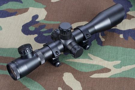 camouflaged: sniper scope on camouflaged uniform background
