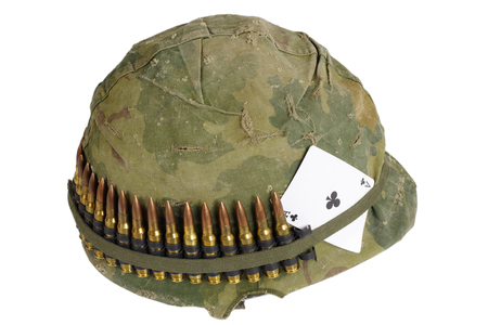 ace of clubs: US Army helmet Vietnam war period with camouflage cover and ammo belt and amulet - ace of clubs playing card
