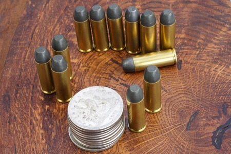 frontier: The .45 Revolver cartridges and Silver Dollar Wild West period on wooden background