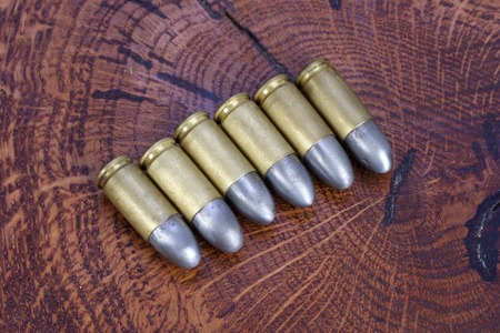 caliber: The 9mm caliber cartridge on wooden background