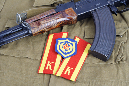 infantry: AK47 with Soviet Army Cadet shoulder mark and Mechanized infantry shoulder patch on khaki uniform background