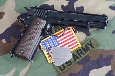 us army: KIEV, UKRAINE - June 6, 2015. US ARMY branch tape, M1911 handgun with dog tags on woodland camouflage uniform
